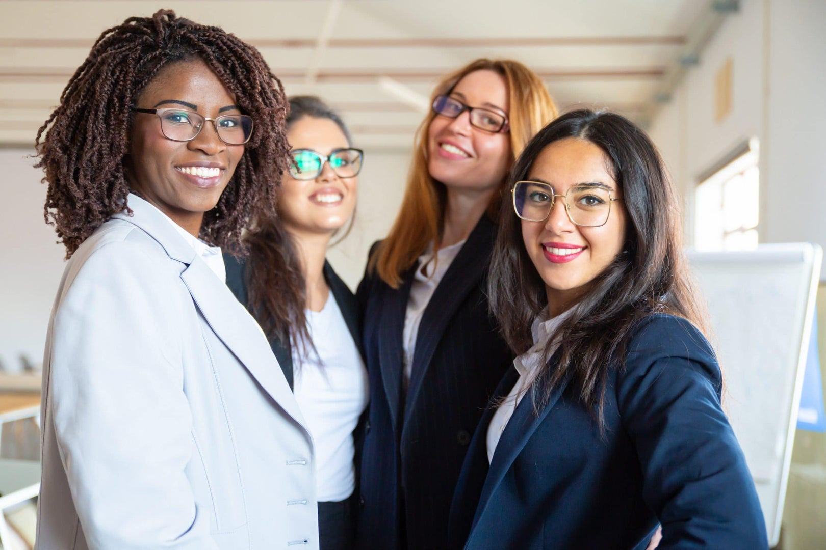 Group of confident young businesswomen looking at camera. Beautiful smiling women posing. Female confidence concept